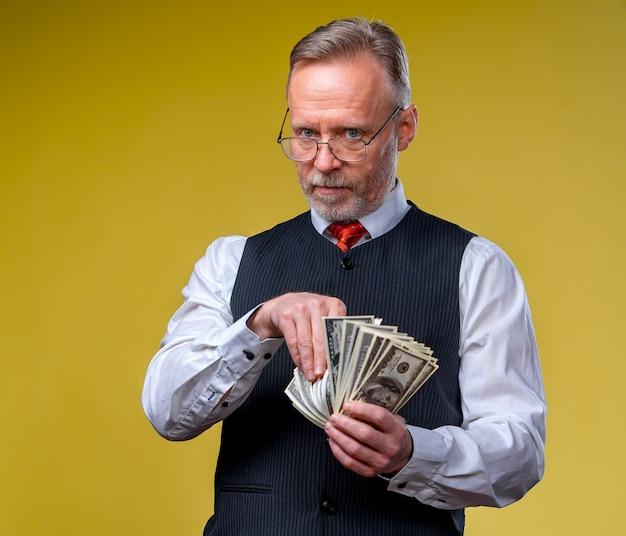 노란색 배경에 고립 된 손에 달러 지폐를 많이 들고 남자
