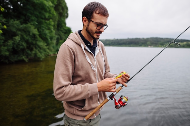 Man holding lure and fishing rod near the lake