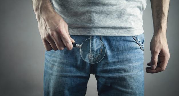 Мужчина держит увеличительное стекло на джинсах.