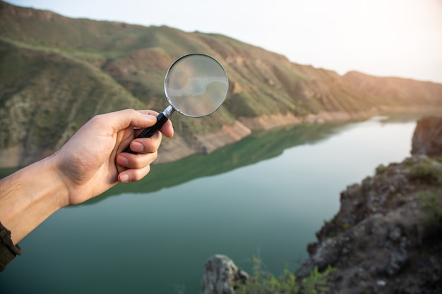 Man holding a magnifying glass on the surface of nature