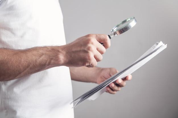 Мужчина держит увеличительное стекло с документами.
