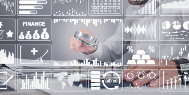 Man holding magnifying glass with a graphs and charts. business. analysis