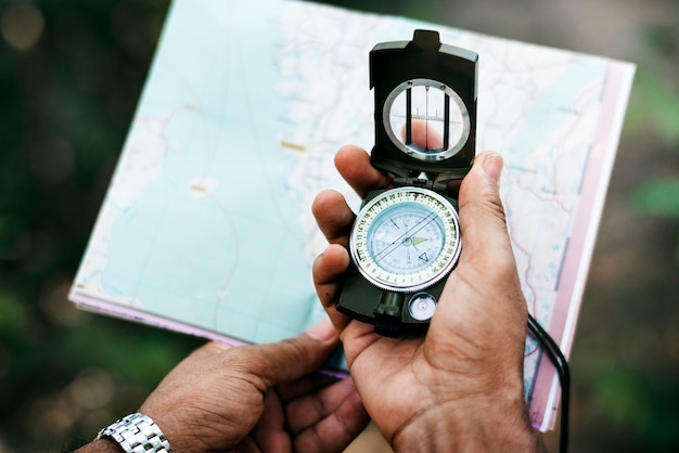 Man holding a map and a compass
