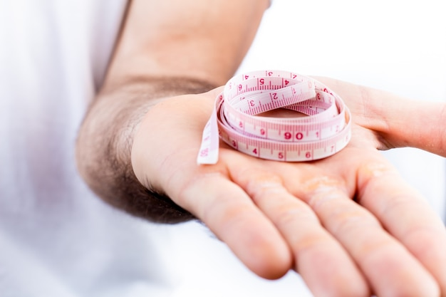 A man holding measuring tape on photo with white background for slimming and healthy life concept