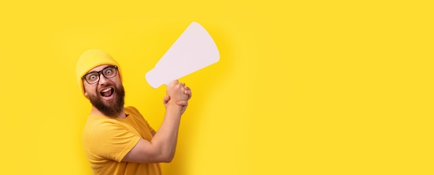 Man holding megaphone over yellow background, panoramic layout with space for text