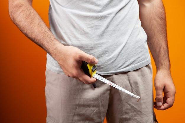 Мужчина держит метр возле пениса на оранжевом фоне