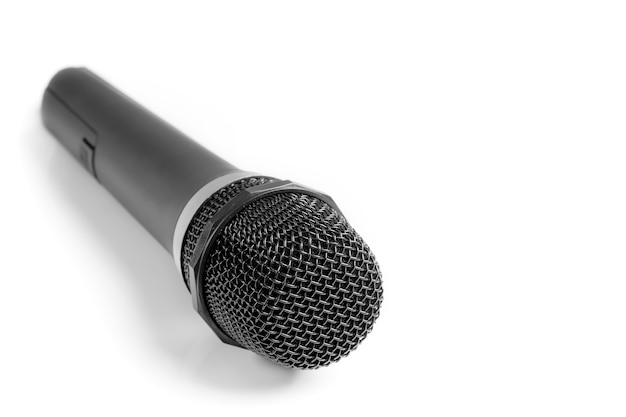 A man holding a microphone on a white surface