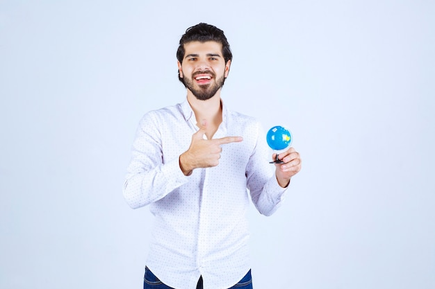 Uomo che tiene un mini globo e lo guarda looking