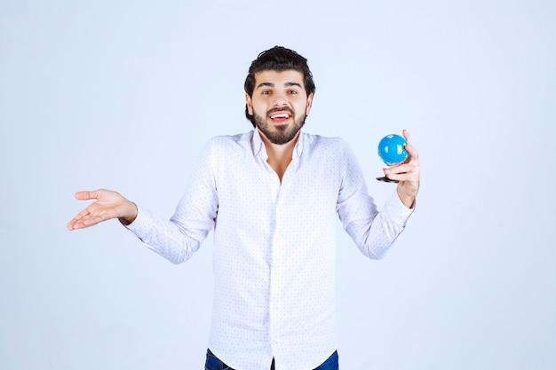 Uomo che tiene un mini globo e sembra confuso