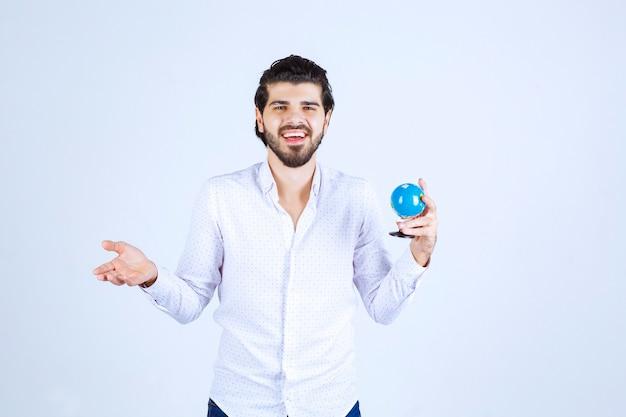 Uomo che tiene un mini globo e sembra confuso Foto Gratuite