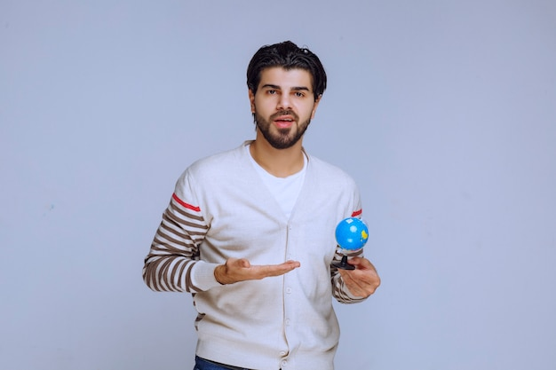 Man holding a mini globe and looks like he has no knowledge on geography.