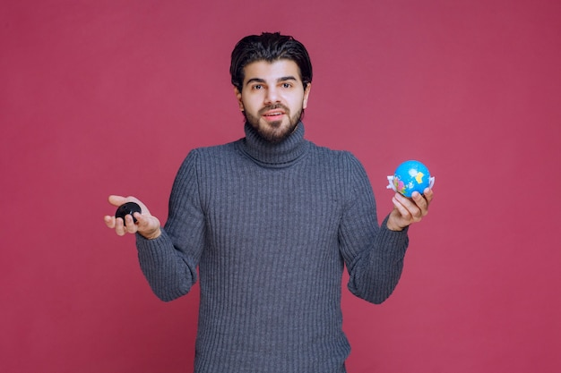 Man holding a mini globe and making a presentation about it.