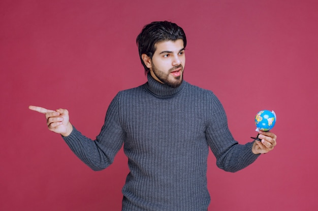 Man holding a mini globe and pointing to the left.