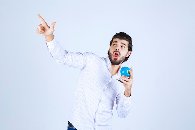 Man holding a mini globe and pointing at somewhere else