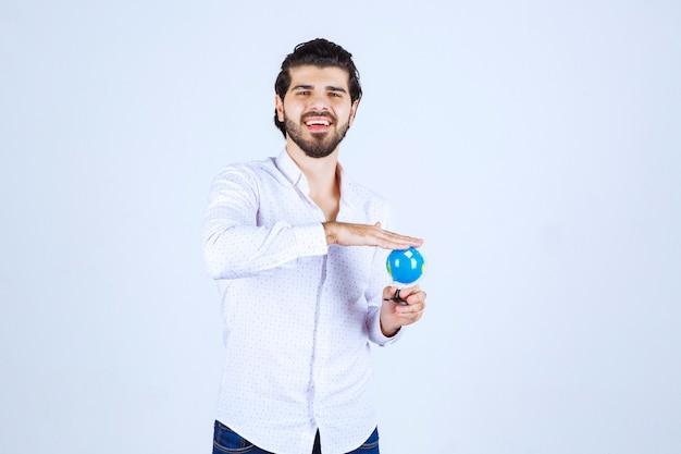 Uomo con in mano un mini mappamondo
