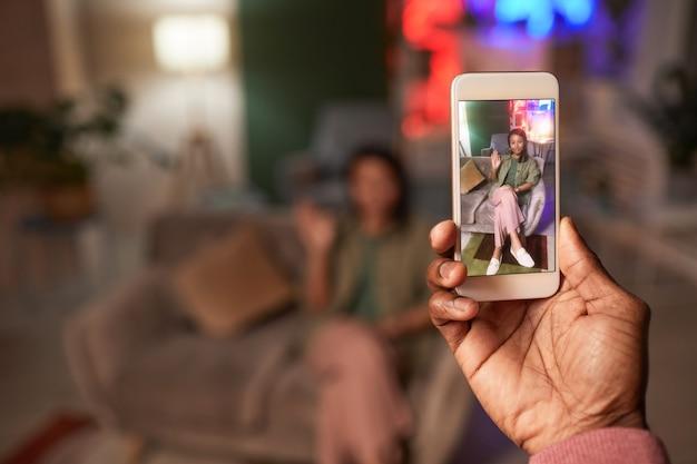 Мужчина держит мобильный телефон, фотографируя молодую женщину, которая позирует на диване