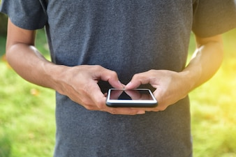 オンラインインターネットでスマートアプリケーションを使用してモバイルスマートフォンを抱きかかえた