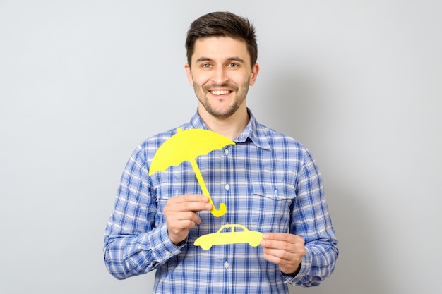 Man holding model of car and yellow umbrella