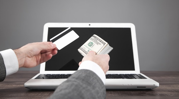 Человек, держащий деньги и кредитную карту над портативным компьютером.
