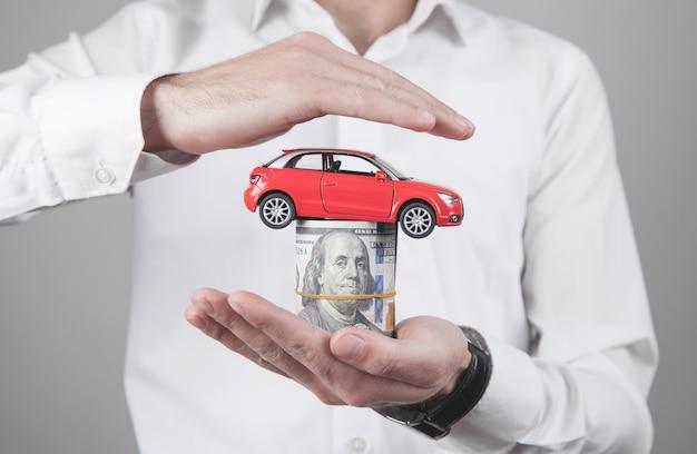 Человек, держащий деньги и красный игрушечный автомобиль.
