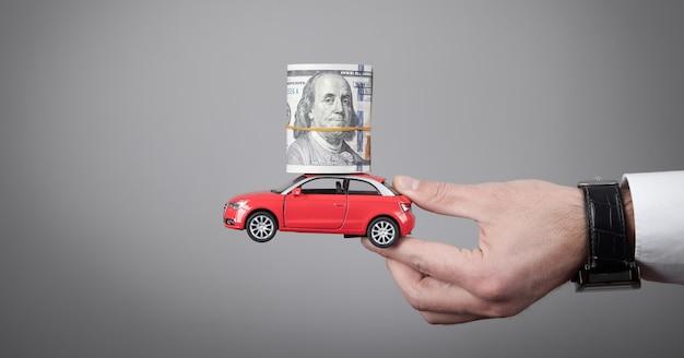 お金と赤いおもちゃの車を持っている男。