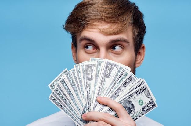 Человек, держащий деньги крупным планом богатство успех синий фон