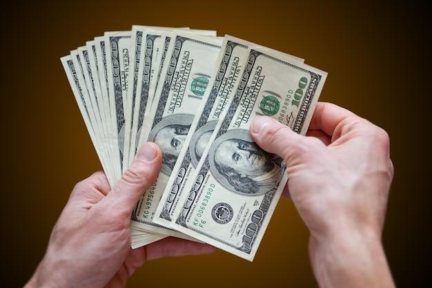 Мужчина держит в руках деньги долларов