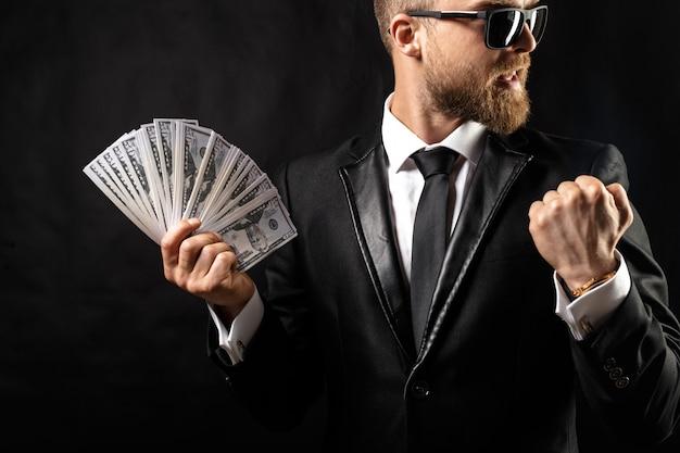 Man holding money in hand on black
