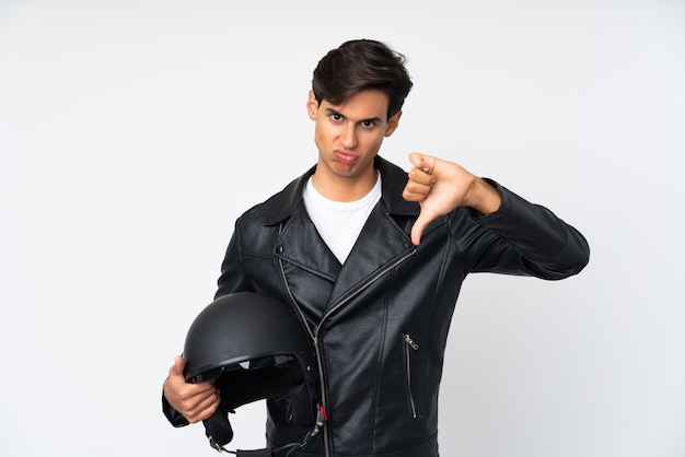 Man holding a motorcycle helmet over white wall showing thumb down sign