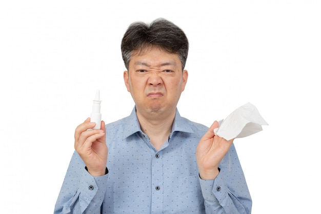 A man holding a nasal spray in his hand on white.