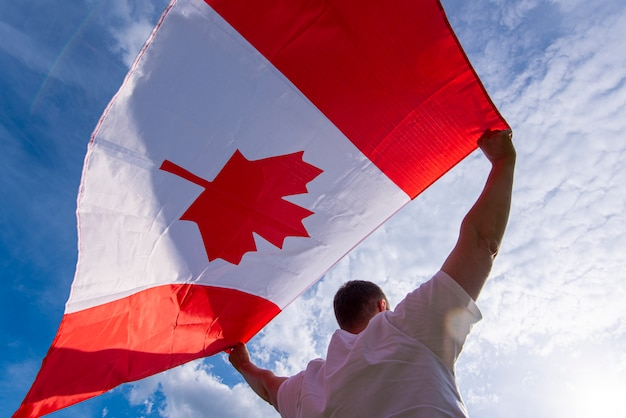Man holding the national flag of canada against blue sky