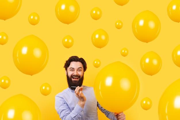 Мужчина держит иглу над желтым воздушным шаром за мгновение до взрыва