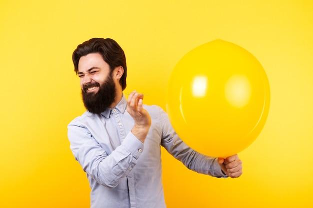 Мужчина держит иглу над желтым воздушным шаром, за мгновение до лопнувшего пузыря