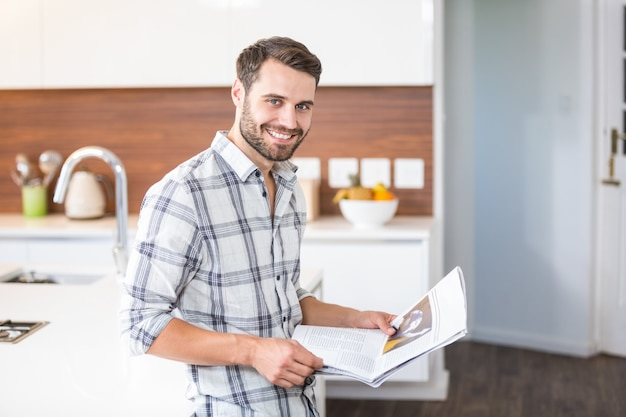 Man holding newspaper while leaning on kitchen counter