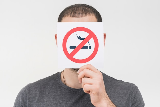 A man holding no smoking sign in front of his face against white backdrop