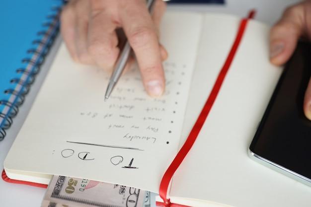 Мужчина держит блокнот со списком дел на сегодня возле концепции домашнего бухгалтерского учета крупным планом мобильного телефона