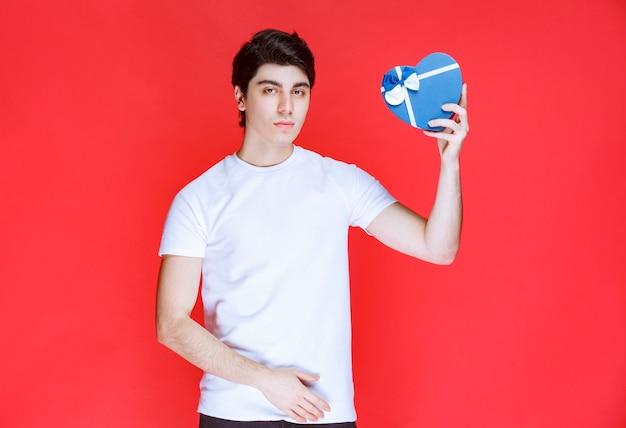 Man holding and offering a heart shape blue gift box.