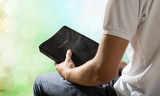 背景に古い聖書の本を持っている男