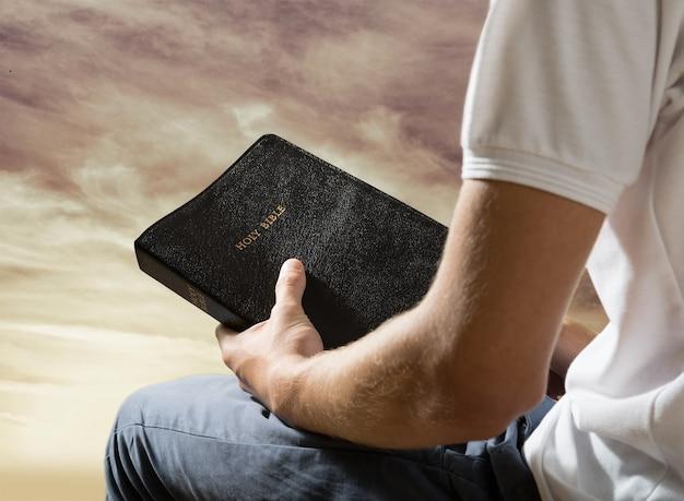 緑の背景に古い聖書の本を持っている男