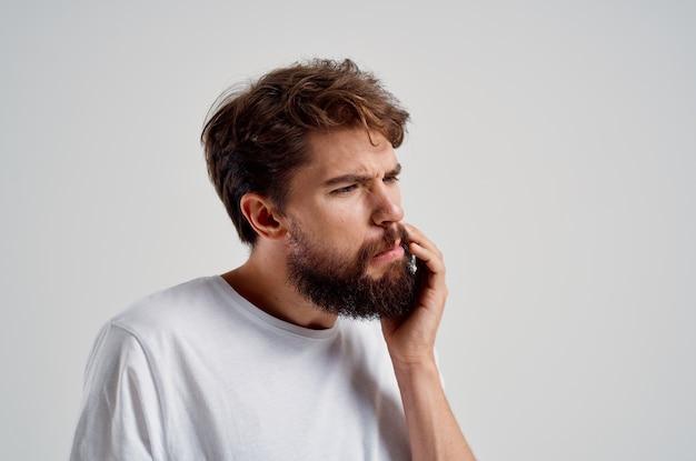 Человек держится за боль в зубах на светлом фоне