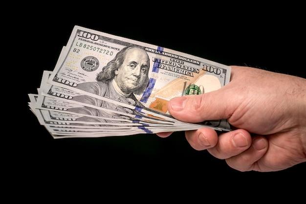 Мужчина держит стодолларовые купюры в руке на черном изолированном фоне