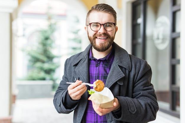 ストリート フード フェスティバルで、ひよこ豆で作った伝統的なおいしいユダヤ料理のファラフェルを使った 1 回限りのプレートを持つ男性。とてもおいしい揚げ菜食。