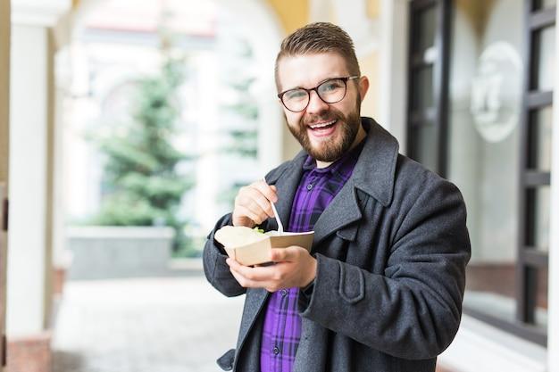 ストリート フード フェスティバルで、ひよこ豆で作った伝統的なおいしいユダヤ料理のファラフェルを使った 1 回限りのプレートを持つ男性。