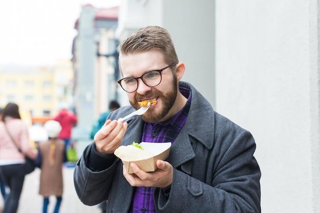 Мужчина держит одноразовую тарелку с традиционным вкусным еврейским фалафелем из нута на фестивале уличной еды.
