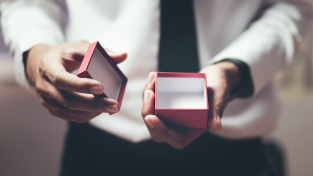 Man holding open the empty red gift box.