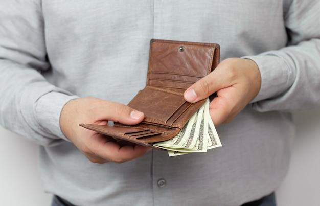 Мужчина держит открытый кожаный кошелек, полный долларов