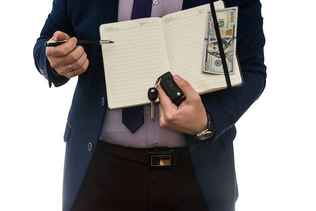Человек, держащий открытый ноутбук подписывает договор купли-продажи или аренды с наличными деньгами, изолированными на белой стене.