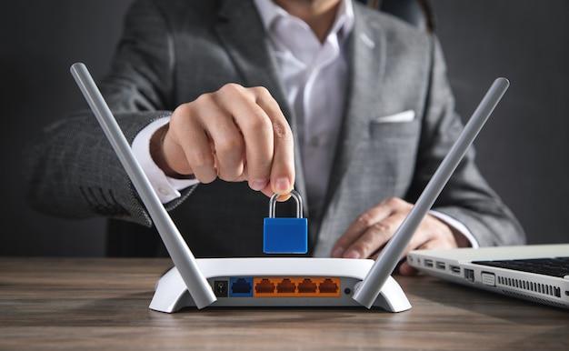 インターネットルーター上で南京錠を保持している男。ネットワーク保護