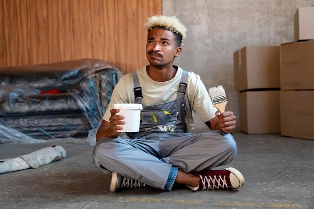 Мужчина держит кисть и ведро, чтобы украсить свой новый дом