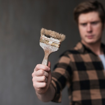 Man holding a painting brush in front of him